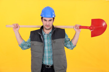 Scowling labourer carrying a shovel
