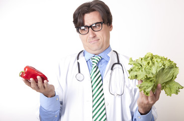 Young attractive man doctor holding green salad and red pepper