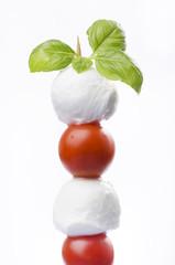 spiedino di pomodorini e mozzarelline con foglie di basilico