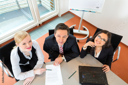 Businesspeople are sitting at office desk