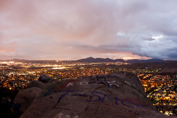 Evening mountaintop view of boulders, clouds, and suburbia