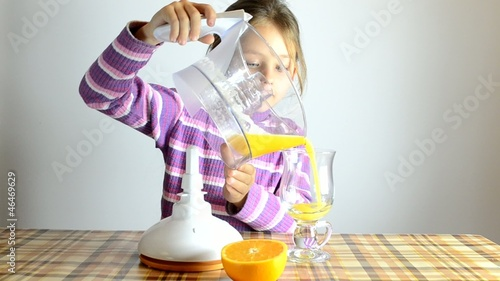 girl pours fresh orange juice from the juicer