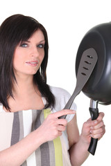 Woman with a spatula and a frying pan