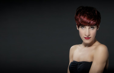 Young woman with red hairs in front of a grey background