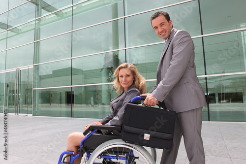 woman in a wheelchair and man helping