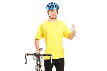 Smiling bicyclist posing next to a bicycle and giving thumb up