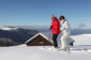 Skiing couple in front of chalet