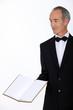 Grey haired restaurant worker presenting menu
