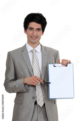 Businessman pointing to a blank clipboard