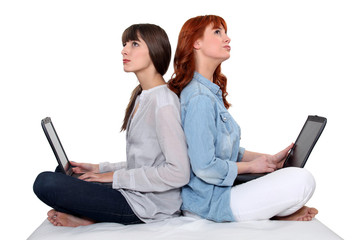 Two female friends sat together each using a laptop computer