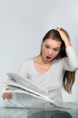 Shocked woman reading a newspaper