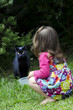 Little girl plays with a cat