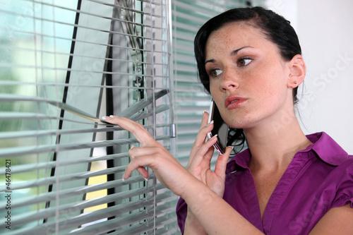 Woman peeking though window blinds