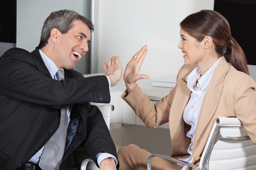 Chef und Mitarbeiterin machen High Five