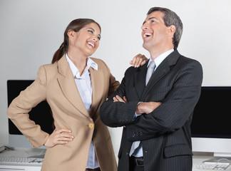 Manager und Sekretärin lachen im Büro