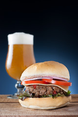 Burger with cheese, onion, tomato and lettuce served with a beer
