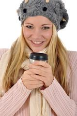 Junge Frau in Winterkleidung trinkt Kaffee