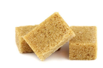 Brown cane sugar lumps on white background