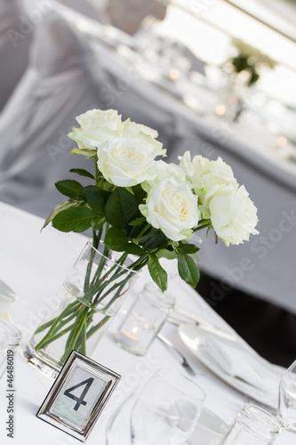 A vase of white roses in and crystal wine glasses.