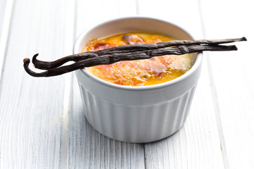 creme brulee in ceramic bowl with vanilla pod