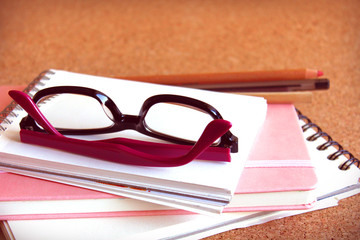 Black and purple glasses and some notebooks.