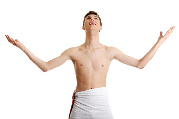 Young man in towel with hands up