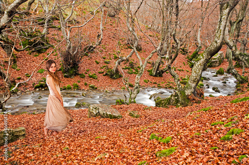 Beautiful girl walking barefoot in the wood in autumn