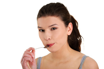 Young smiling woman with spoon in her mouth
