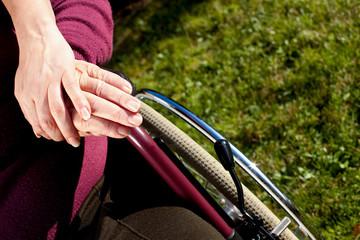 Mehrere Hände berühren sich, eine Person sitzt im Rollstuhl