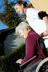 Pflegerin schiebt Seniorin im Rollstuhl durch einen Garten