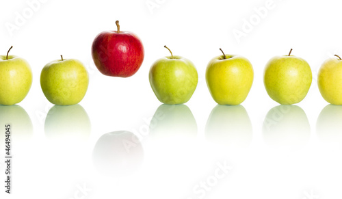 Red apple standing out from row of green apples.