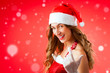 Attractive young woman in Santa Claus costume alluring gesture