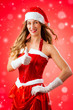 Attractive young woman in Santa Claus costume with thumbs up