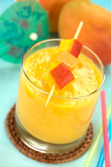 Fresh mango juice in glass with mango pieces on skewer