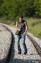 young man walking on railroad