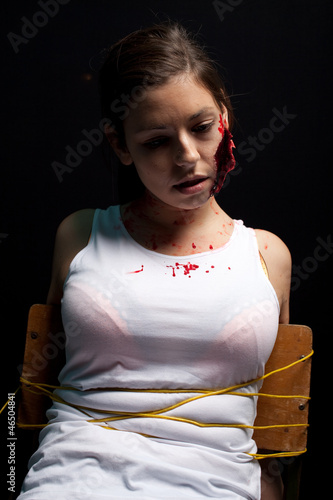 Kidnapped and tortured young woman with a big cut on her face, t