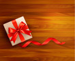 Holiday background with gift box and red ribbons.