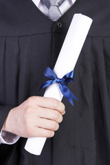 Midsection of a man in graduation gown holding diploma