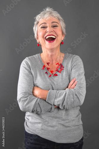 Lachende ältere Dame in Grau