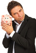 Businessman listening to piggy bank