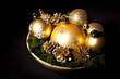 gold christms glass balls with pinecones over dark