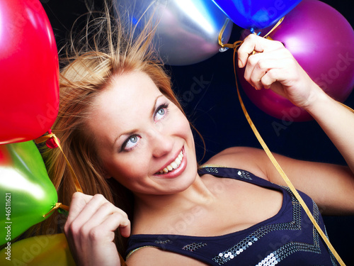 blond woman holding ballons and celebrating