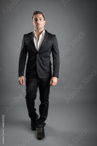 Young man full body portrait against grey background.