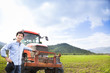 happy asian farmer with Old tractor on the grass field