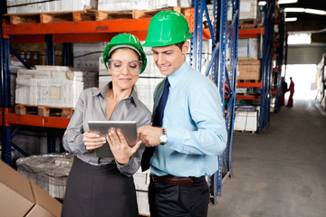 Supervisors Using Digital Tablet At Warehouse