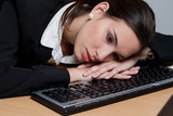 Overworked tired businesswoman falling asleep on the keyboard
