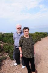 Happy elderly seniors couple standing on path under blue sky