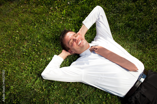 Businessman lying in the grass and relaxing