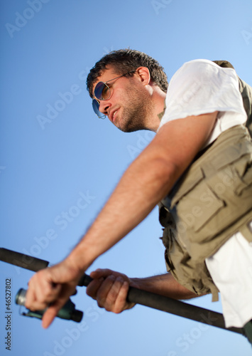 Handsome man fishing. Shot against clear blue sky.
