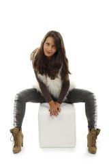 Junge Frau sitzt frontal auf weißem Hocker